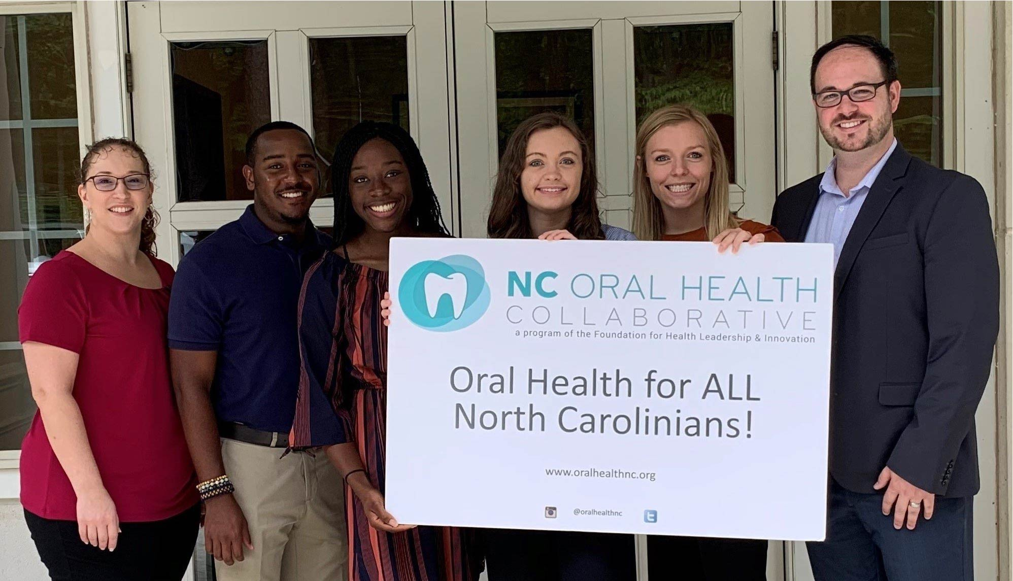 """Picture with Campbell University public health students and NCOHC staff holding """"Oral Health for All"""" sign"""