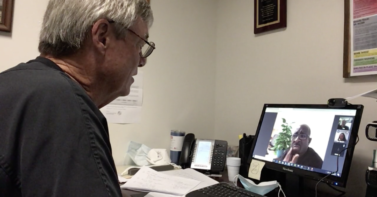 Picture of Dr. Rob Doherty talking to a patient via a computer webcam